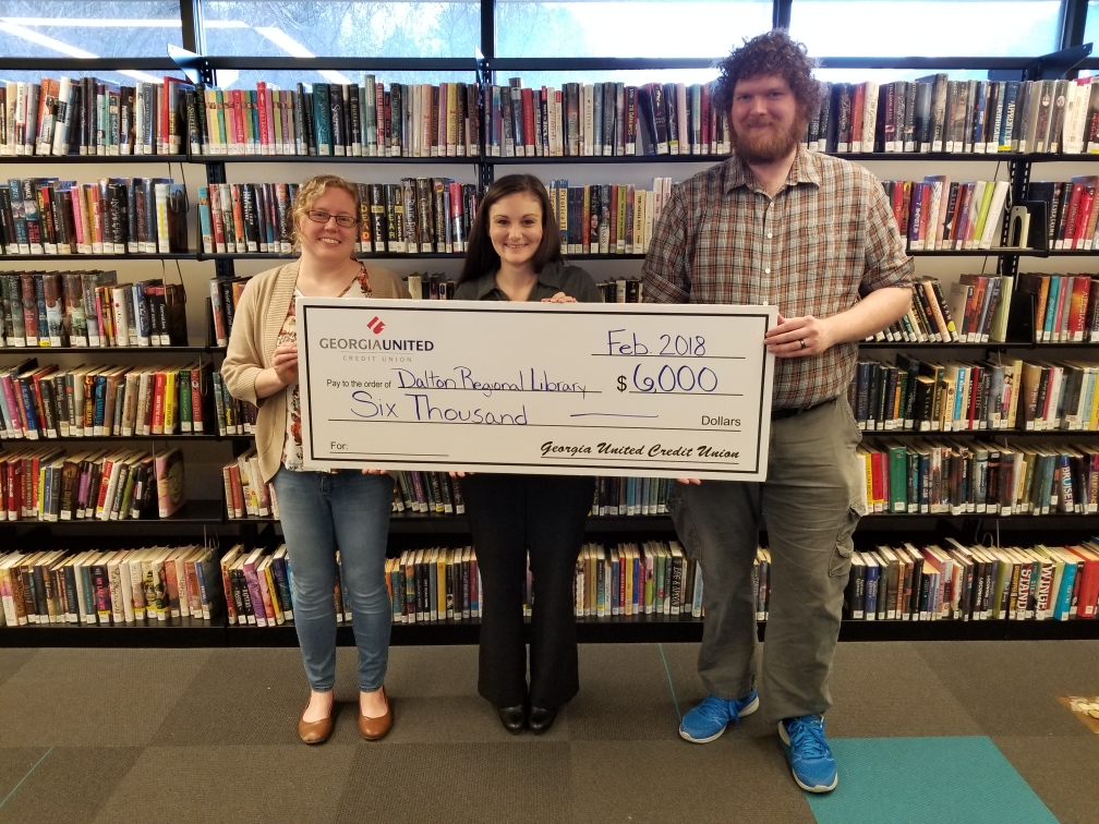 Library staff with Georgia United Credit Union member holding a giant check for the Math Tutoring Program.