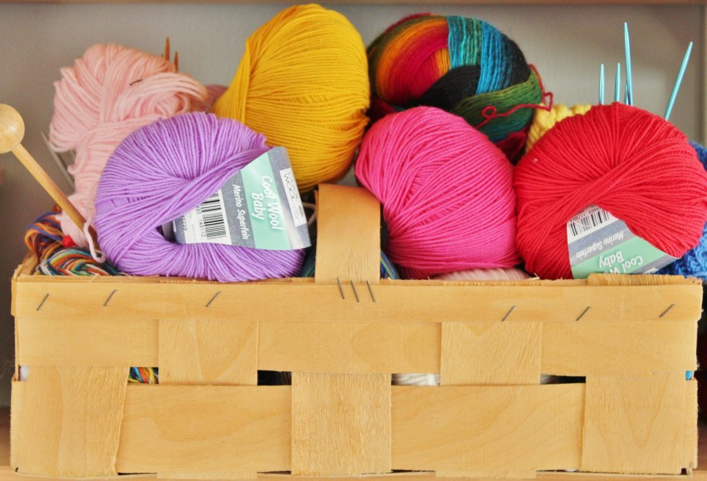 Colorful skeins of yarn in a basket.